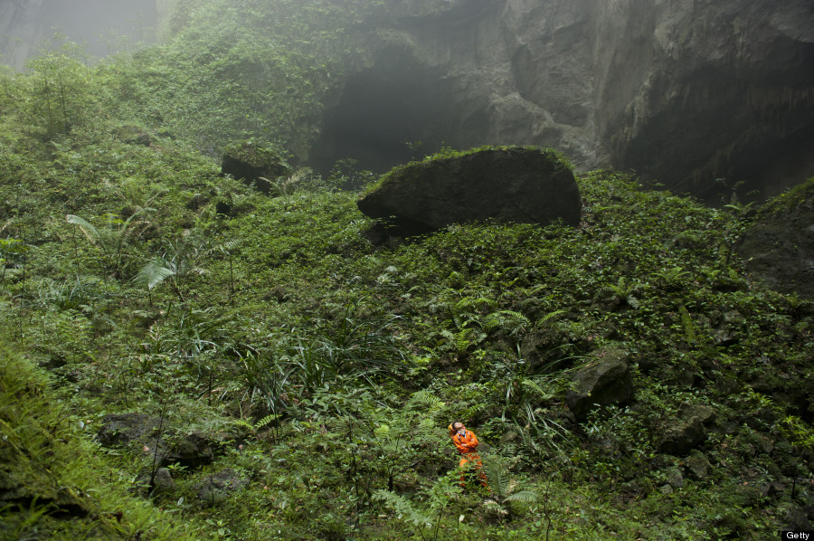 VIETNAM - APRIL 30: A Hang Son Doong explorer navigates an plant-covered cavescape. Phong Nha Ke Bang National Park, Vietnam. (Photo by Carsten Peter/National Geographic/Getty Images)
